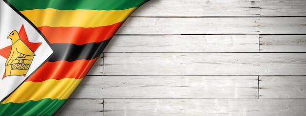 Flaga zimbabwe na starej białej ścianie. poziomy baner panoramiczny.