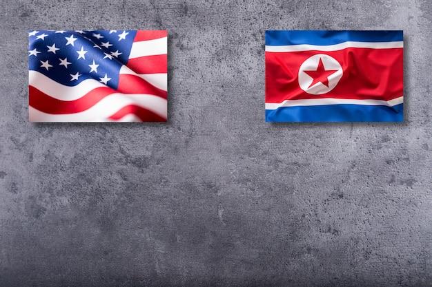 Flagi ameryki i korei północnej. flaga usa i korei północnej na tle konkretnych.