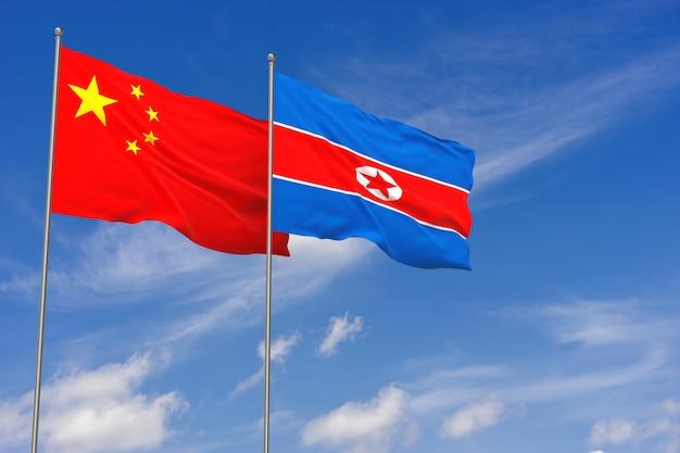 Flagi chin i korei północnej na tle błękitnego nieba. ilustracja 3d