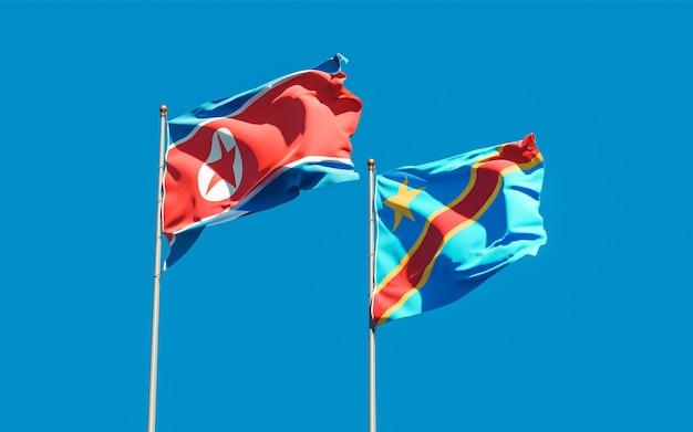 Flagi korei północnej i dr konga na błękitnym niebie. grafika 3d