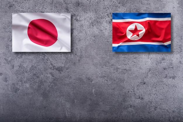 Flagi korei północnej i japonii. flaga korei północnej i japonii na betonowym tle.