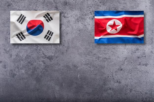 Flagi korei północnej i korei południowej. flaga korei północnej i korei południowej na betonowym tle.