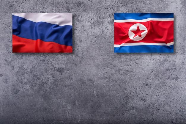 Flagi korei północnej i rosji. flaga korei północnej i rosji na betonowym tle.