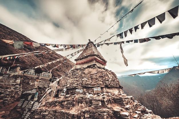 Flagi modlitewne i buddyjska stupa na trasie trekkingowej do everest base camp. himalaje, nepal. piękny widok z doliny khumbu, solukhumbu, park narodowy sagarmatha. tonowanie w stylu retro vintage