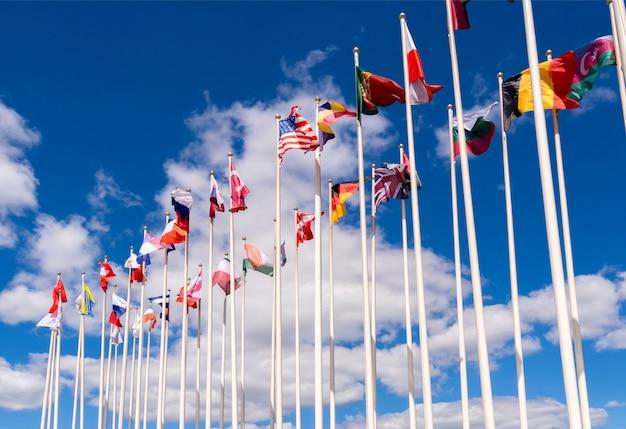 Flagi narodowe na masztach. flagi stanów zjednoczonych, niemiec, belgii, włoch, izraela, turcji