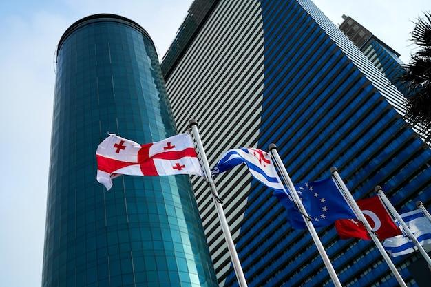 Flagi państw na masztach na tle nowoczesnych drapaczy chmur.