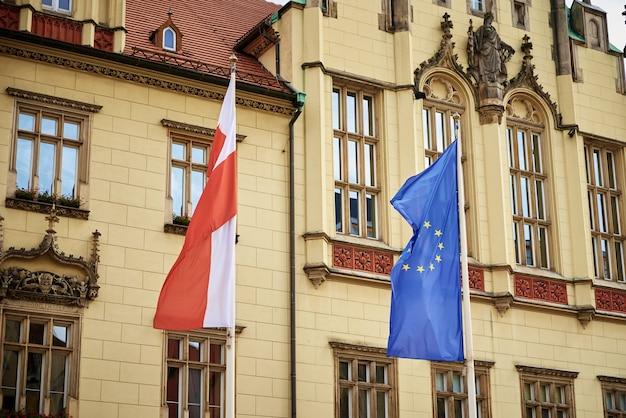 Flagi polski i unii europejskiej powiewają na masztach