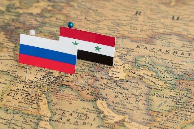 Flagi rosji i syrii na mapie świata. fotografia koncepcyjna, polityka i porządek świata