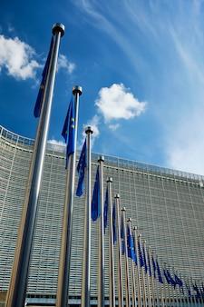 Flagi unii europejskiej ue przed budynkiem komisji europejskiej w tle. brussles, belgia