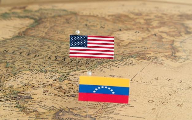 Flagi usa i wenezueli na mapie świata. fotografia koncepcyjna, polityka i porządek świata