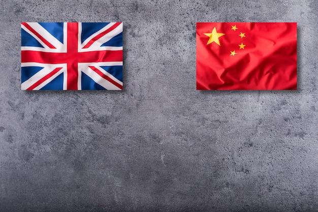 Flagi zjednoczonego królestwa i chin na betonowym tle.