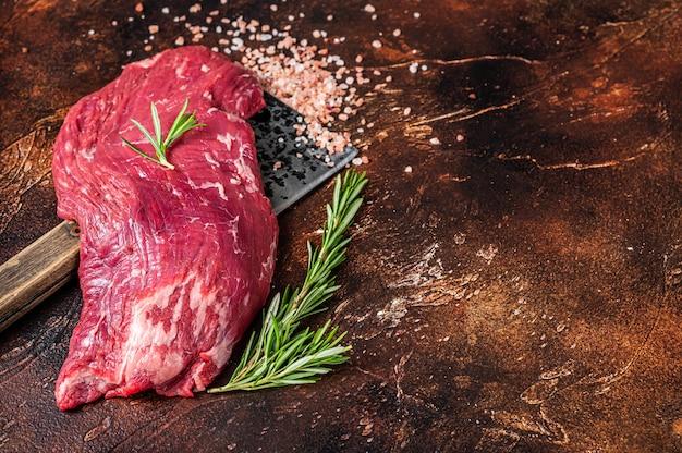 Flap lub flank stek z surowej wołowiny na tasaku rzeźniczym z ziołami. ciemne tło. widok z góry. skopiuj miejsce.