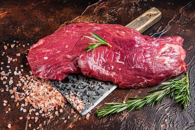 Flap lub flank stek z surowej wołowiny na tasaku rzeźniczym z ziołami. ciemne tło. widok z góry.