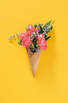 Flat lay ice cream cone z kolorowym bukietem na żółtym, kopia przestrzeń