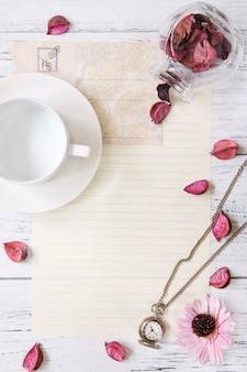 Flat lay stock photography fioletowy kwiat płatki list koperta papier przezroczysta szklana butelka kieszonkowy zegar filiżanka herbaty