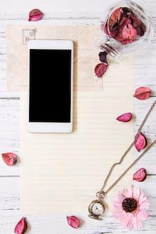 Flat lay stock photography fioletowy kwiat płatki list koperta papierowa butelka szklana inteligentny telefon makieta zegar kieszonkowy