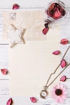 Flat lay stock photography purpurowy kwiat płatki list koperta papierowa przezroczysta szklana butelka kieszonkowy zegar star craft