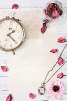 Flat lay stock photography purpurowy kwiat płatki list koperta papierowa przezroczysta szklana butelka kieszonkowy zegar