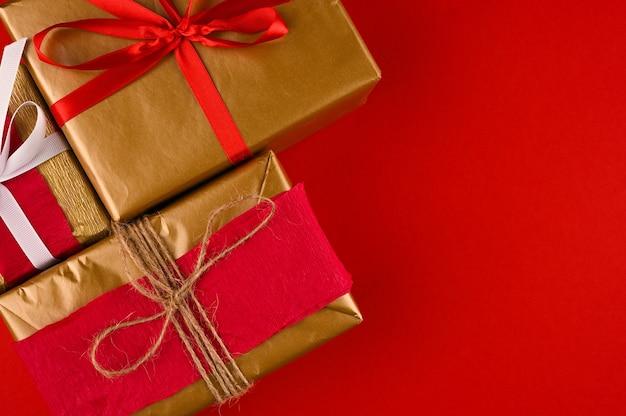 Flat lay z pudełkami na prezenty, wstążkami, dekoracjami w czerwonych kolorach.