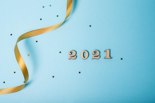 Flatlay christmas. 2021 z liczb. układ nowego 2021. drewniane numery. witam nowy rok. artykuł o nowym roku i bożym narodzeniu. układ klawiatury. skopiuj miejsce. gwiazdy. niebieskie tło.
