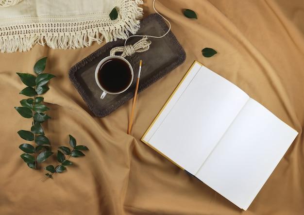 Flatlay otwartej książki z filiżanką kawy na łóżku