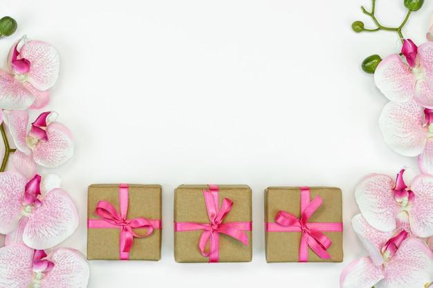 Flatlay prezent teraźniejszość boksuje z różową faborkiem i orchidea kwitnie na białym tle
