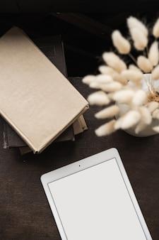 Flatlay pustego ekranu tabletu, książek, puszystej trawy króliczej opowieści na brązie