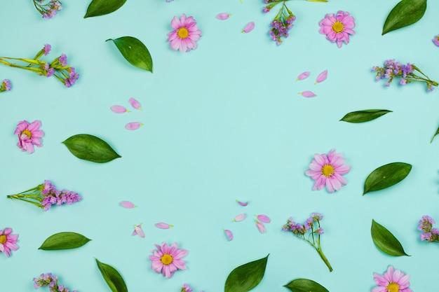 Flatlay rama kwiatowy tło z stokrotki, kwiaty, płatki i liście, niebieskie tło. copyspace
