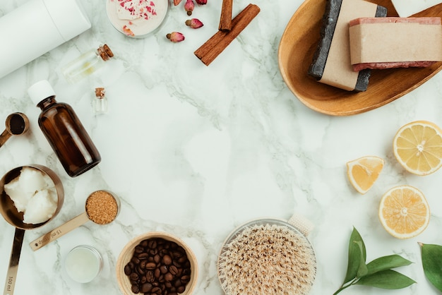 Flatlay różnych naturalnych domowych kosmetyków i składników: olejków eterycznych, kawy, cukru, mydła