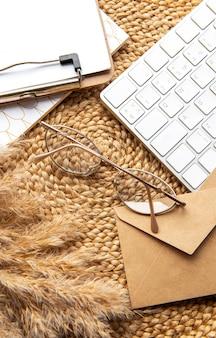 Flatlay schowka z czystym arkuszem papieru. klawiatura, trawa pampasowa, artykuły papiernicze na beżowym słomianym tle. minimalistyczne biurko do pracy w domu. widok z góry makieta miejsca kopii.