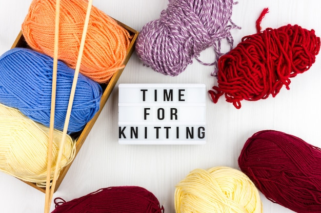 Flatlay wielobarwnych motków przędzy i igieł dziewiarskich z napisem - czas na drutach