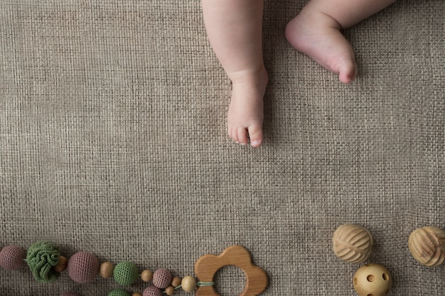 Flatlay z małymi, pulchnymi nóżkami noworodka oraz ręcznie robionymi zabawkami z dzianiny i drewna.