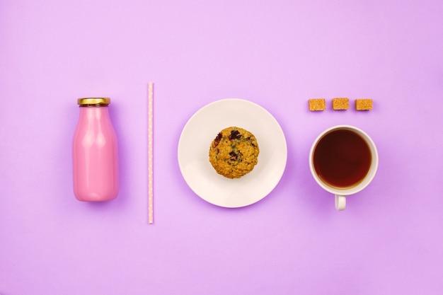 Flatlay z muffinką jagodową, filiżanką herbaty, kostkami cukru trzcinowego i butelką soku