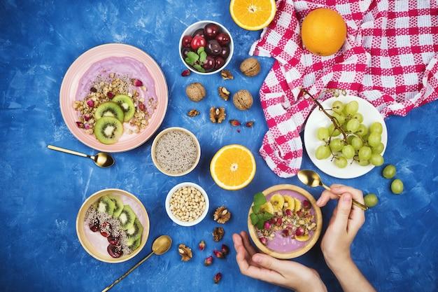 Flatlay ze zdrowym wegańskim śniadaniem z jagodowego jogurtu na bazie muesli, nasion chia, różnych owoców i orzechów włoskich na niebieskim tle