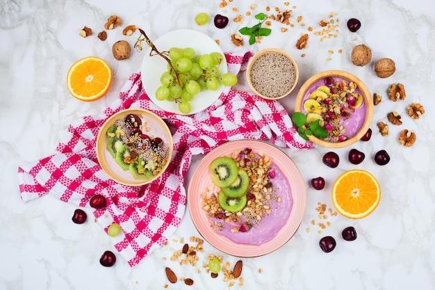 Flatlay ze zdrowym wegańskim zestawem śniadaniowym na marmurowym tle. kokosowe i drewniane miski z koktajlami, jogurtem na bazie roślin, nasionami chia i innymi składnikami
