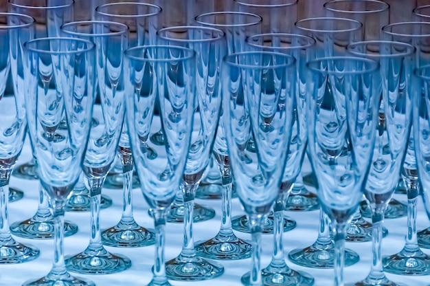 Flety szampana na jasnoniebieskiej przezierności w nowoczesnym stylu. zbliżenie kilku na stole.