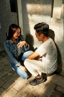 Flirtuje uśmiechnięty młody mężczyzna i kobieta, patrząc na siebie, śmiejąc się i rozmawiając