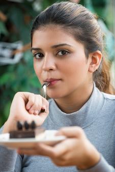 Flirty kobieta jedzenia tort i spojrzenie na aparat fotograficzny