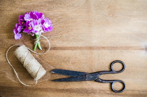 Florystyczny tło. kwiaty, nożyczki i liny.