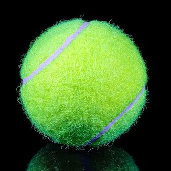 Fluorescencyjna żółta piłka tenisowa trawnik na czarnym tle