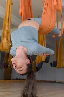 Fly joga bliska sportowa kobieta wisi do góry nogami z zamkniętymi oczami