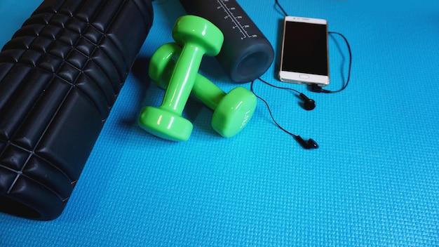 Foam roller z zielonymi hantlami i bidonem oraz telefonem ze słuchawkami - gym fitness equipment niebieskie tło self myofascial release - mfr.