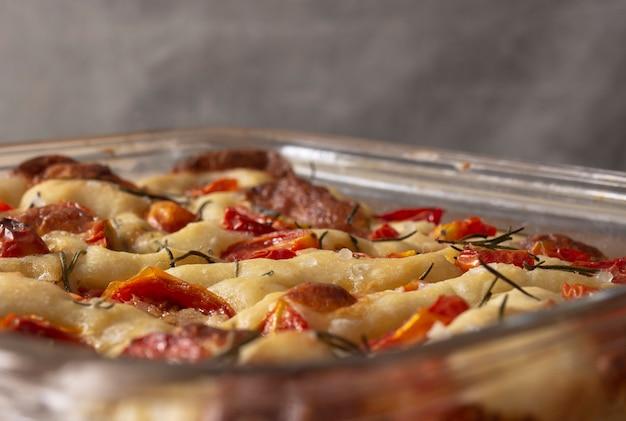 Focaccia z rozmarynem, oliwą z oliwek i pomidorem na drewnianym stole. makro