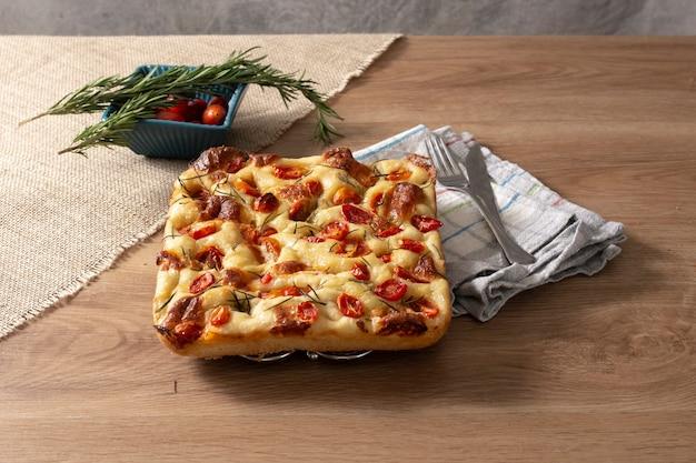 Focaccia z rozmarynem, oliwą z oliwek i pomidorem na drewnianym stole.