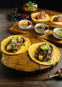 Foie gras tacos serwowane na drewnianej desce do krojenia z różnymi sosami i meksykańskim suszonym ch