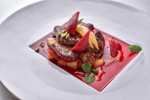 Foie gras w sosie truskawkowym z kawałkami gruszki i truskawek na białym talerzu