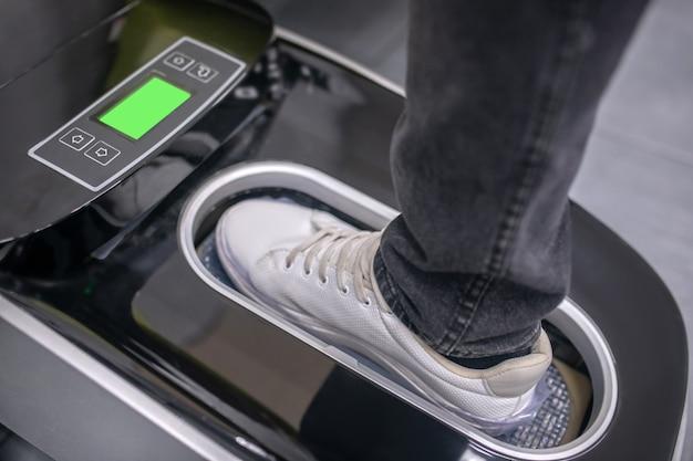 Folia termiczna. stopa w tenisówkach, stojąca w specjalnym aparacie na platformie opuszczona i automatycznie zakładająca pokrowiec na buty