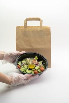 Foliowane talerze z jedzeniem w ręce kobiety, obok papierowej torby na białej ścianie