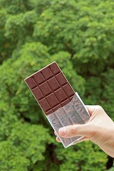 Foliowe opakowanie batonika czekoladowego w dłoni z rozmytymi zielonymi liśćmi w tle