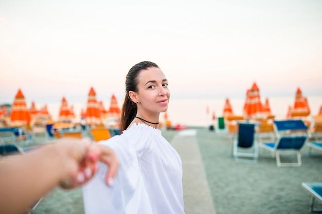 Follow me pov - zakochana para bawi się. chłopak dziewczyny po trzymając się za ręce na plaży uśmiecha się korzystających z aktywnego trybu życia na świeżym powietrzu w monterosso. koncepcja follow me
